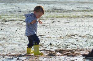 enfant en bottes bord de mer